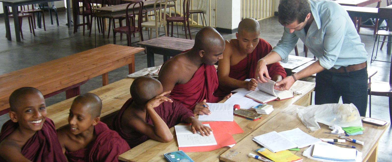 A volunteer helps his students with their classwork during his teaching work experience in Sri Lanka